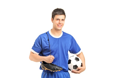 soccer shoes: A smiling footballer in sport wear holding a soccer shoes and football isolated on white background