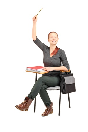 A studio shot of a female student sitting on a chair and raising her hand isolated against white background photo