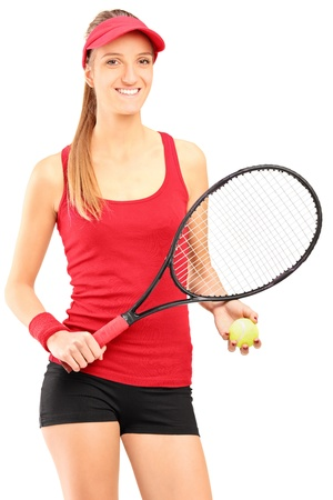 A young female tennis player holding a racket and ball isolated against white background photo