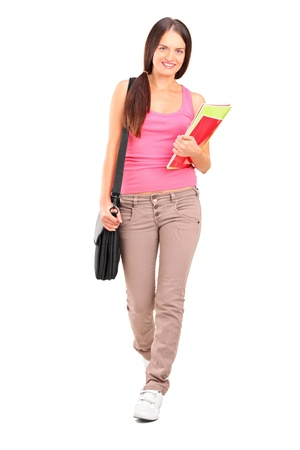 studio shots: Full length portrait of a female student with shoulder bag and books walking isolated on white background