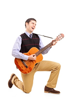 Full length portrait of a male playing a guitar and singing isolated against white background photo
