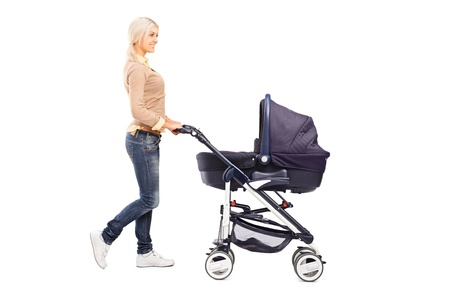 Full length portrait of a mother pushing a baby stroller isolated against white background photo
