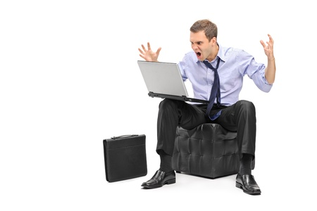 A nervous young businessman screaming on his laptop isolated against white background Stock Photo - 16882495