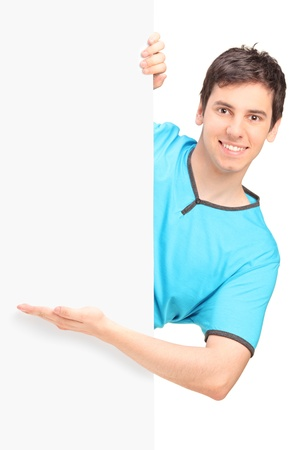 A smiling handsome male gesturing behind a blank panel isolated against white background photo