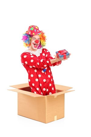 Smiling clown in a cardboard box holding a gift isolated on white background Stock Photo - 16882507
