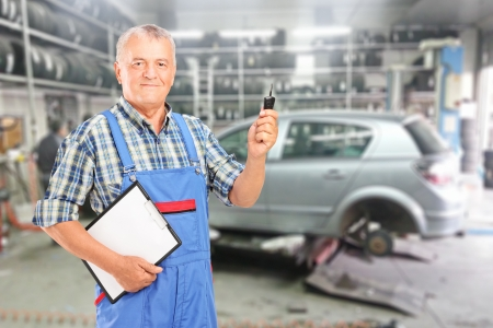 Mature auto mechanic with clipboard and car key in front of modern car during automobile maintenance at auto repair shop