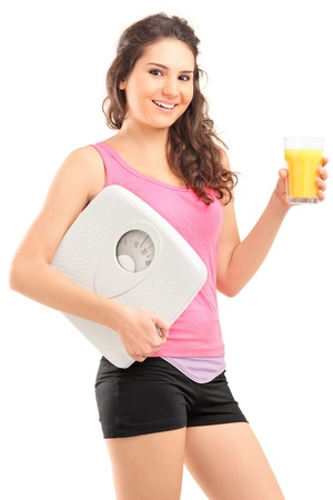 A smiling female athlete holding a weight scale and glass of orange juice isolated on white background Stock Photo - 16890645