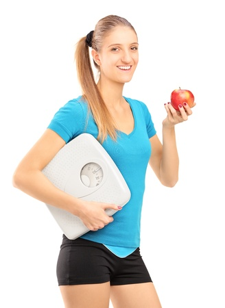 A smiling female athlete holding a weight scale and red apple isolated on white background photo
