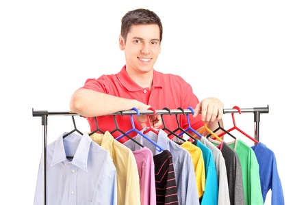 clothes rail: A smiling guy posing on a hang rail full of clothes isolated on white background