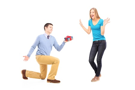 Full length portrait of a male on knee giving a gift to his excited girlfriend isolated on white background photo
