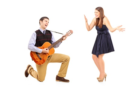 A male playing on a guitar and singing to his girlfriend isolated against white background photo