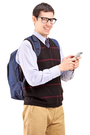 A smiling student with backpack typing a sms on a mobile phone isolated on white background photo