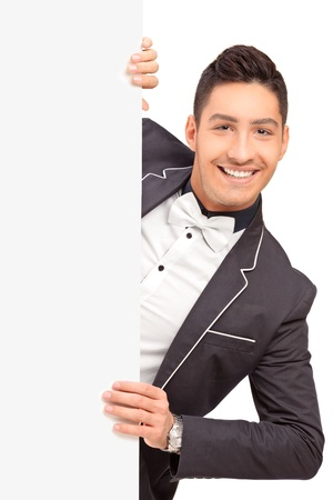 A stylish handsome guy posing behind a blank panel isolated on white background photo