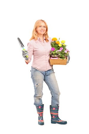 Full length portrait of a female gardener holding flowers and gardening equipment isolated on white background photo