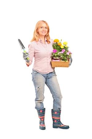 Full length portrait of a female gardener holding flowers and gardening equipment isolated on white background