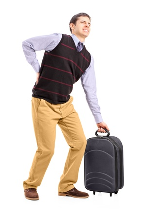 levantar peso: Retrato de cuerpo entero de un hombre que levanta su equipaje y que sufre de un dolor de espalda aislado sobre fondo blanco