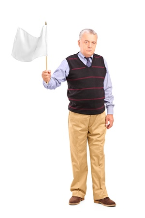 Full length portrait of a sad senior man waving a white flag isolated on white background photo