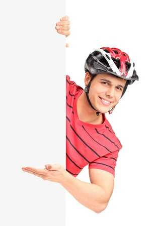 Portrait of a male bicyclist wearing helmet and gesturing behind a white panel isolated on white background Stock Photo - 16953844