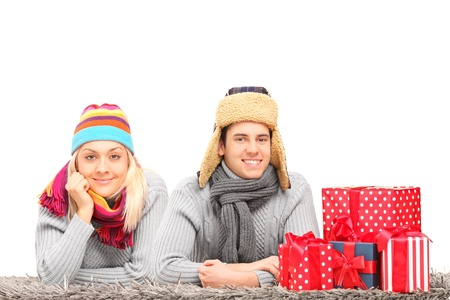 A happy couple with hats and neckwears lying on a carpet near presents isolated on white background photo