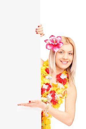 A smiling woman wearing hawaian costume and gesturing on a blank panel isolated on white background Stock Photo - 16981258