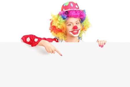 Female clown with happy joyful expression pointing with finger on a blank panel isolated on white background photo