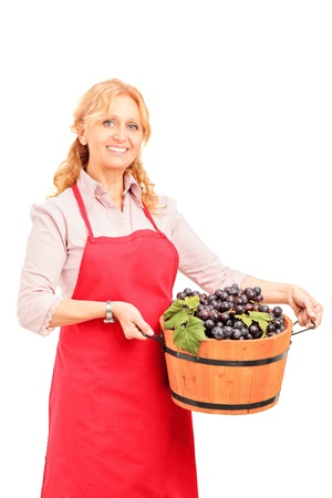 A female vintner holding a basket full of wine grapes isolated on white background photo