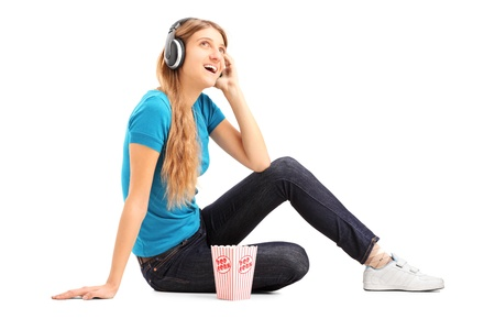 Blond female listening a music and eating popcorn isolated on white background photo