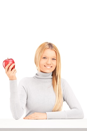 A smiling blond female holding a red apple on a table isolated on white background photo