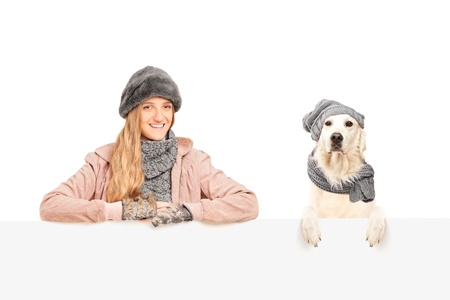 A smiling female posing with labrador retriever dog behind a blank panel Stock Photo - 16999969