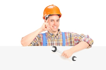 Satisfied male construction worker standing behind a blank panel with a wrench in his hand photo