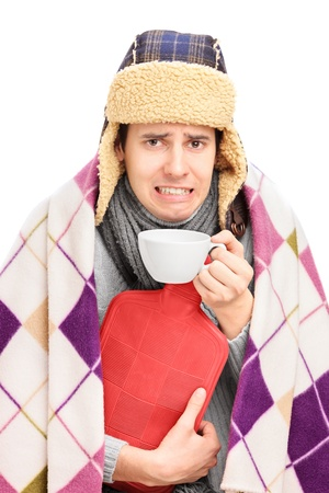 Sick guy covered with blanket holding a hot-water bottle and drinking a tea isolated on white photo