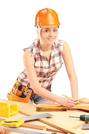 serrucho: Carpintero Mujer con el casco en el trabajo aislado en el fondo blanco