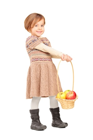 Full length portrait of a cute little girl holding a basket with apples isolated on white background photo