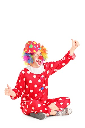 Funny circus clown sitting ang giving thumbs up isolated on white background Stock Photo - 17000366
