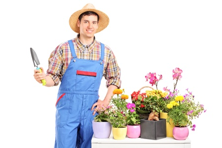 Male gardener holding a spade and posing next to a table full of flower pot isolated on white background Stock Photo - 17007025