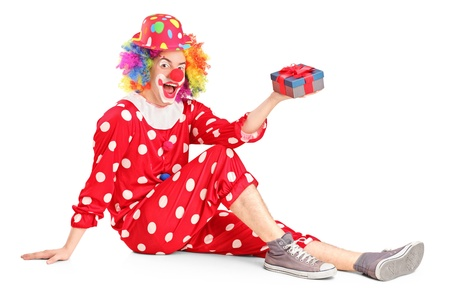 A smiling clown on a floor holding a gift isolated on white background Stock Photo - 17098937