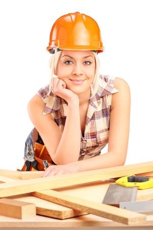 serrucho: Carpintero Mujer con casco posando en el lugar de trabajo aislado en el fondo blanco Foto de archivo