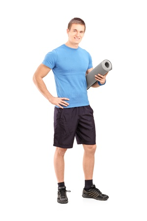 athletic wear: Full length portrait of a male athlete holding a mat isolated on white background
