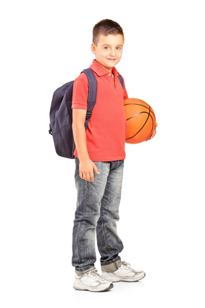 Full length portrait of a school boy with backpack holding a  basketball isolated on white background photo
