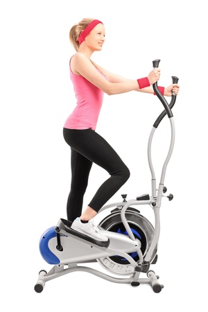Full length portrait of a female athlete working on a cross trainer machine isolated on white background