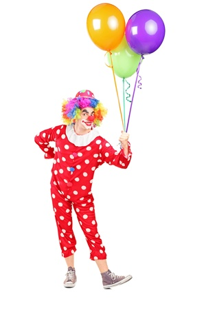 Full length portrait of a male clown in costume holding bunch of balloons isolated on white background Stock Photo - 17052562