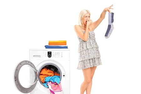 laundry concept: A housewife holding a male sock and her nose next to a washing machine isolated on white