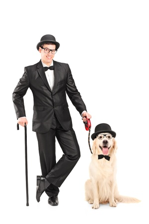 Full length portrait of a magician with bow tie holding cane and dog isolated on white background Stock Photo - 17052572