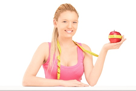 A smiling female holding a red apple wrapped with measuring tape isolated on white background photo