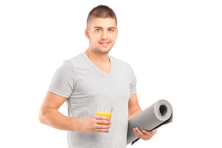A male holding a glass of orange juice and a mat after an excerise isolated on white Stock Photo - 17130839