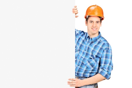 A male worker with helmet posing behind a blank panel isolated on white background Stock Photo - 17130875