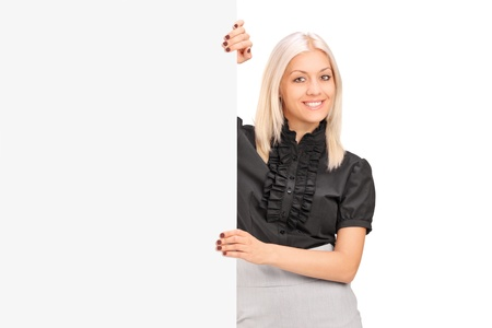 A smiling woman posing next to a blank panel isolated on white photo