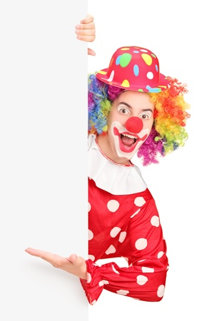 A male clown gesturing on a blank panel isolated on white background Stock Photo - 17135458