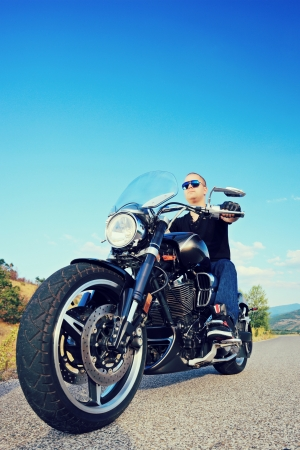 open road: Biker riding a customized motorcycle on an open road Stock Photo