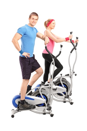 Full length portrait of two athletes on a cross trainer machine isolated on white background Stock Photo - 17135453